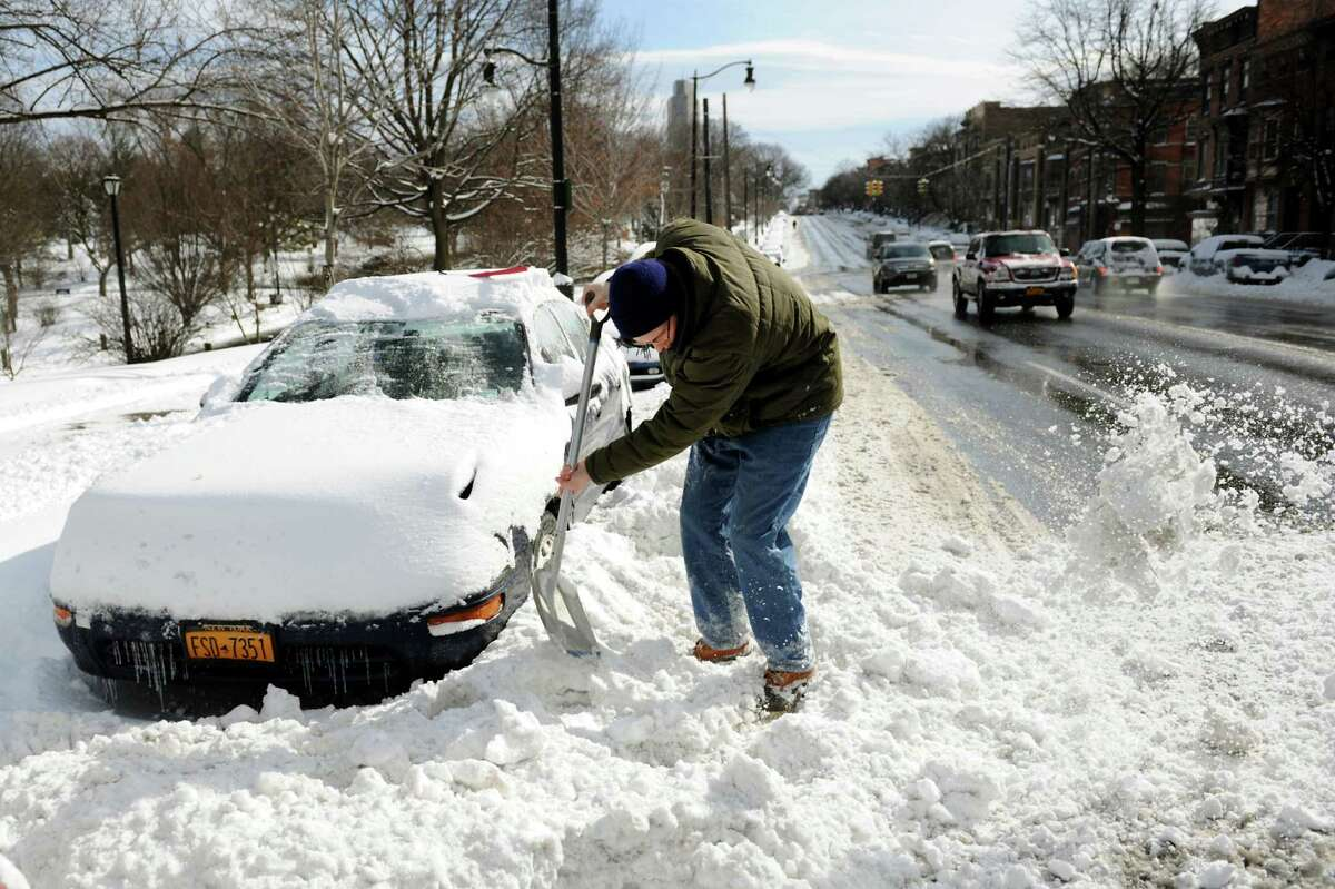 Sean Kite digs out his car along Madison Avenue after a snowstorm on Saturday, Feb. 9, 2013, in Albany, N.Y. (Cindy Schultz / Times Union)