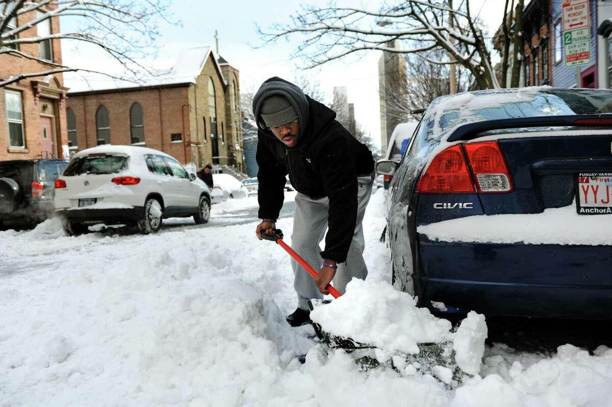 Irani DeAranjo helps dig out a car in Center Square after a snowstorm on Saturday, Feb. 9, 2013, in Albany, N.Y. (Cindy Schultz / Times Union)