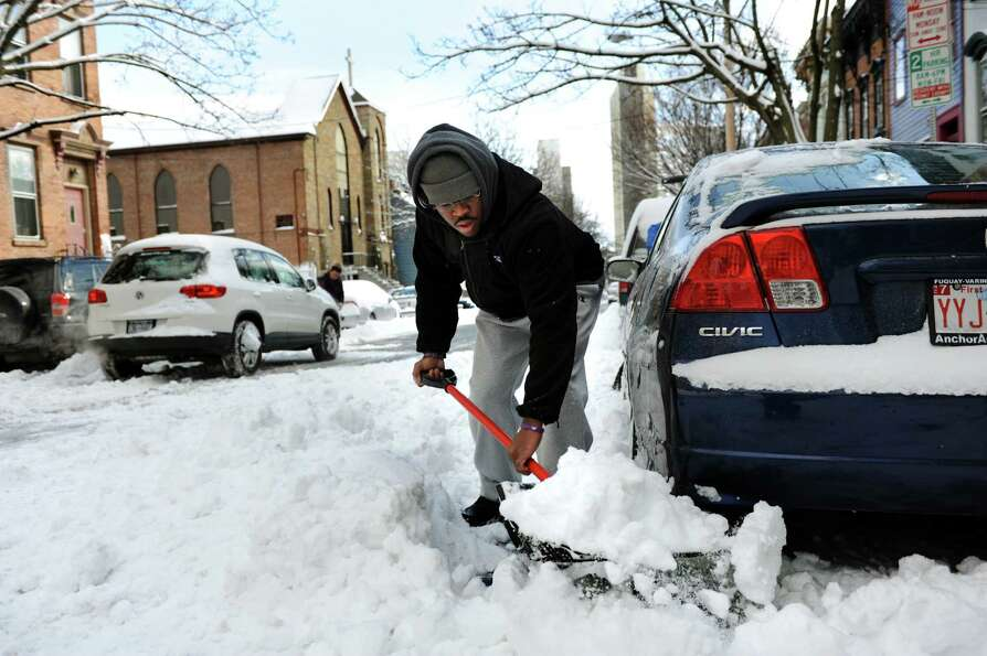 Irani DeAranjo helps dig out a car in Center Square after a snowstorm on Saturday, Feb. 9, 2013, in