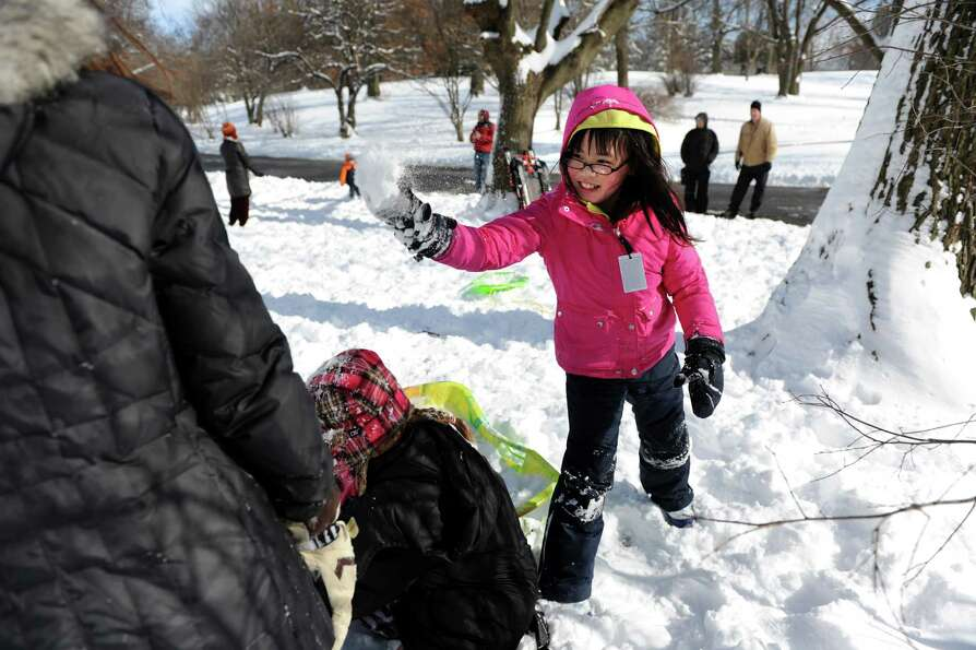 Nora Ebersman-Rant, 9, throws a snowball as she plays in the fresh snow with friends on Saturday, Fe
