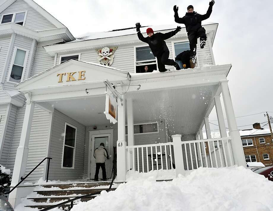 From left, Worcester Polytechnic Institute freshmen Kyle Foster and Steven Como, both members of the Tau Kappa Epsilon fraternity, jump from the fraternity house porch roof into a steep snow bank on Wachusett Street in Worcester, Mass., in the aftermath of an overnight storm on Saturday, Feb. 9, 2013.  Photo: Paul Kapteyn, Associated Press
