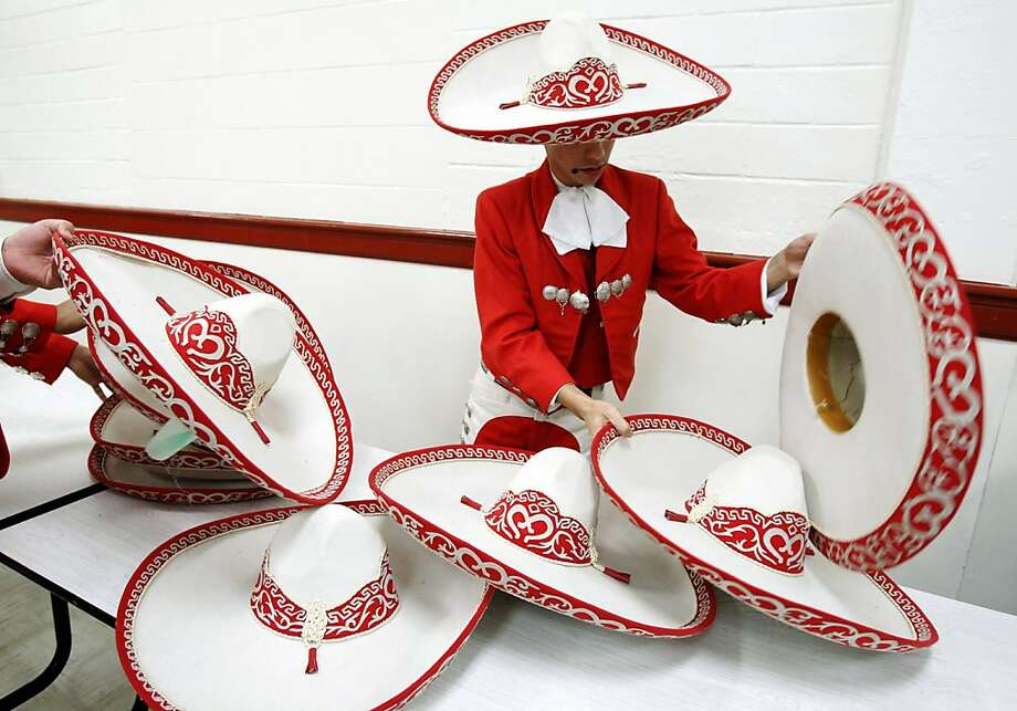 Premont junior David Arredondo sorts through sombreros for the right fit as members of Mariachi Estrella from Premont High School prepare to perform in the Texas High School Mariachi Competition, Saturday, Feb. 9, 2013, in San Antonio.  Photo: Michael Zamora, Associated Press