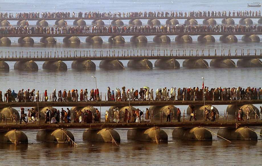 "Thousands of Indian Hindu devotees walk across a pontoon bridge at Sangam, before bathing at the confluence of the Rivers Ganges, Yamuna and mythical Saraswati, during Maha Kumbh festival, in Allahabad, India, Saturday, Feb. 9, 2013. Millions of Hindu pilgrims are attending the Maha Kumbh festival, and over 25 million are expect to take a holy dip at Sangam on Sunday, Feb. 10, on the greatly auspicious occasion of ""Mauni Amavasya.""  Photo: Rajesh Kumar Singh, Associated Press"