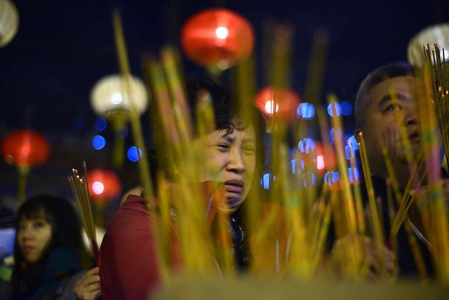 Worshipers place incense sticks as they pray before midnight to welcome in Chinese Lunar New Year at the Wong Tai Sin Temple in Hong Kong on February 9, 2013. Chinese lunar new year, celebrated by Chinese communities the world over, falls on February 10 with the beginning of the new moon.  Photo: Antony Dickson, AFP/Getty Images