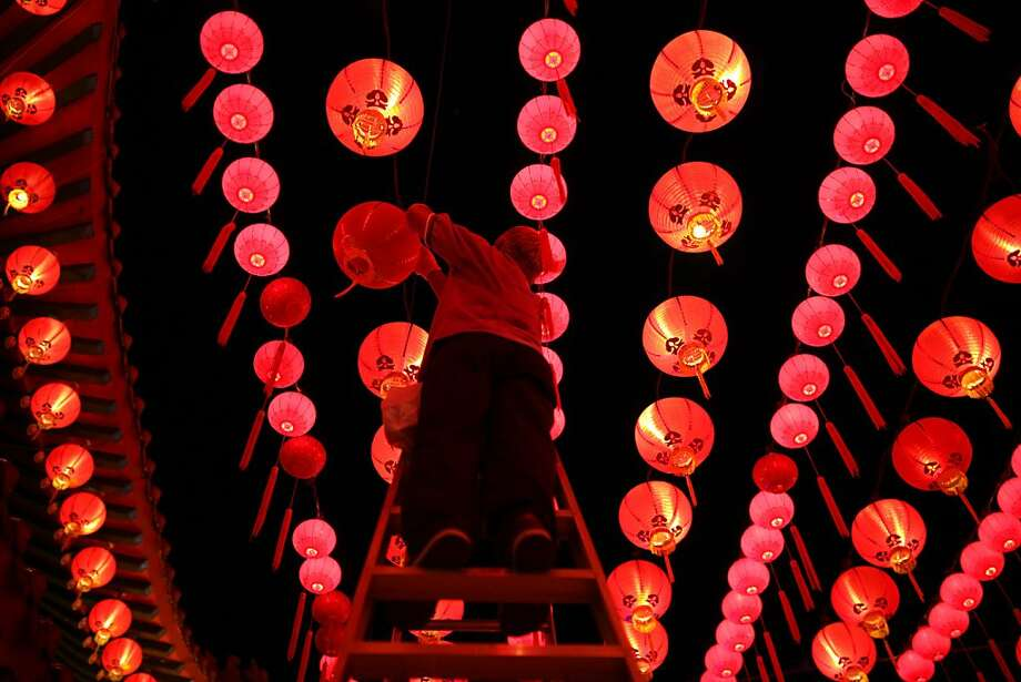 A worker changes the lights bulbs in lanterns ahead of Chinese New Year celebrations at the Thean Hou Temple in Kuala Lumpur on February 9, 2013. Chinese New Year which is also known as Lunar Year falls on February 10.  Photo: Mohd Rasfan, AFP/Getty Images