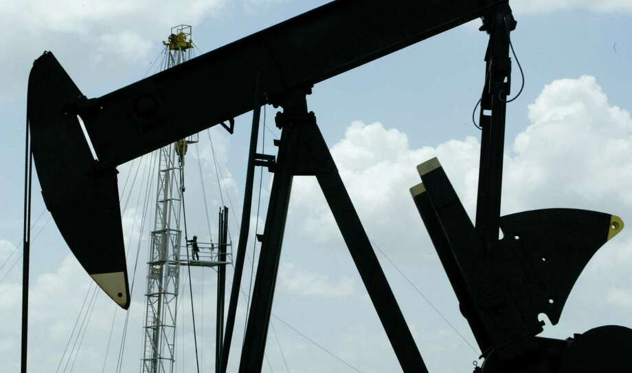 A roughneck stacks pipe on a workover rig while a pumpjack pumps oil from the Brookshire Dome oil field. Photo: Buster Dean, Staff / Houston Chronicle