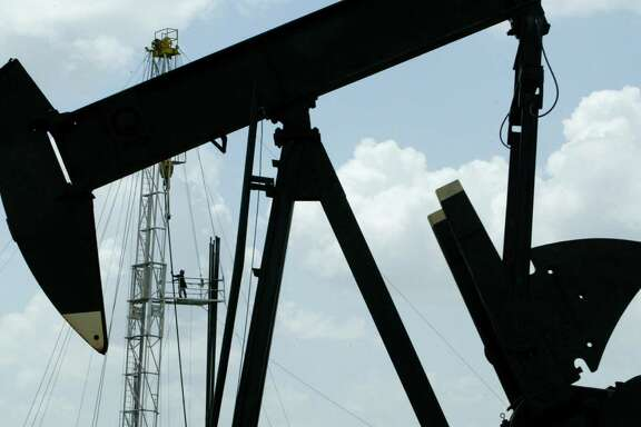 A roughneck stacks pipe on a workover rig while a pumpjack pumps oil from the Brookshire Dome oil field.