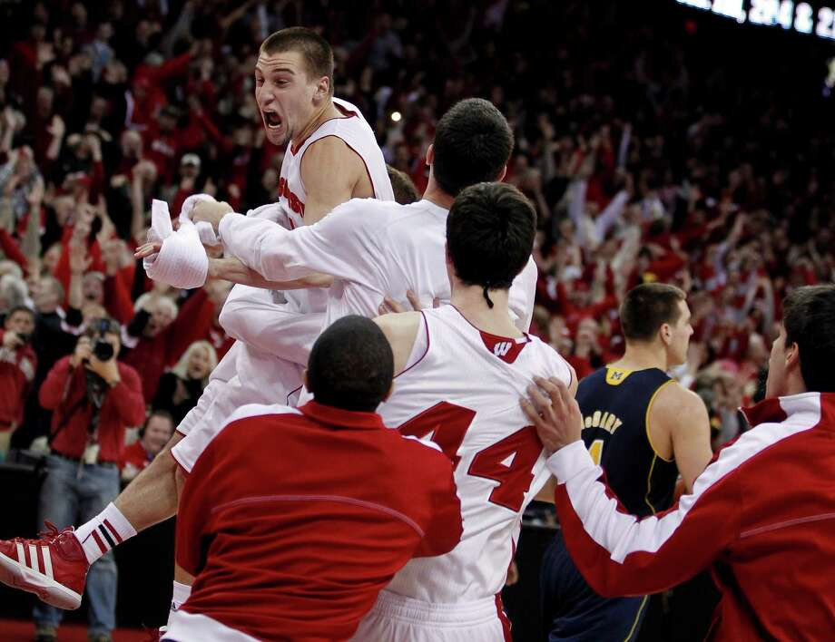 Wisconsin's Ben Brust, top, celebrates after hitting the game-winning 3-pointer to beat Michigan on Saturday. Photo: Andy Manis, FRE / FR19153 AP