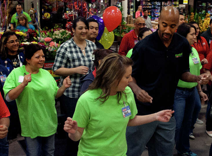 Valerie Cartright (front) and former San Antonio Spur Bruce Bowen(right) join H-E-B officers, employ