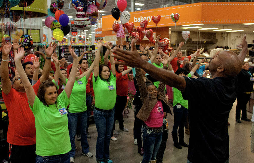 Former San Antonio Spur Bruce Bowen (right) leads H-E-B officers, employees and customers in a stret
