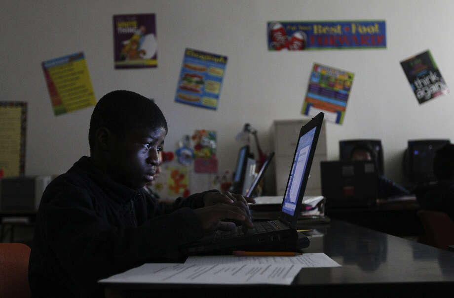 Wachiba Selemani, 13, works on a PowerPoint presentation at NEISD's Jackson Middle School. His family is from the Democratic Republic of Congo, which has seen nearly a decade of armed conflict, and he grew up in a refugee camp. Photo: Photos By Kin Man Hui / San Antonio Express-News