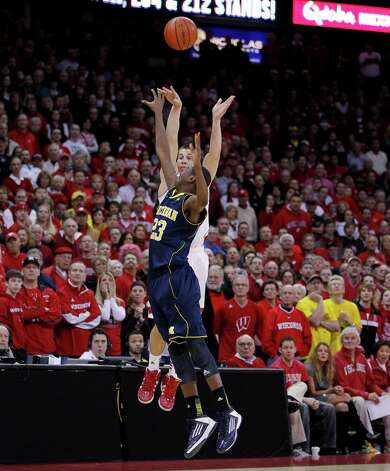 Wisconsin's Ben Brust, top, shoots a 3-point basket against Michigan's Caris LeVert in the final second of regulation to tie the NCAA college basketball game Saturday, Feb. 9, 2013, in Madison, Wis. Wisconsin defeated Michigan 65-62. (AP Photo/Andy Manis) Photo: Andy Manis