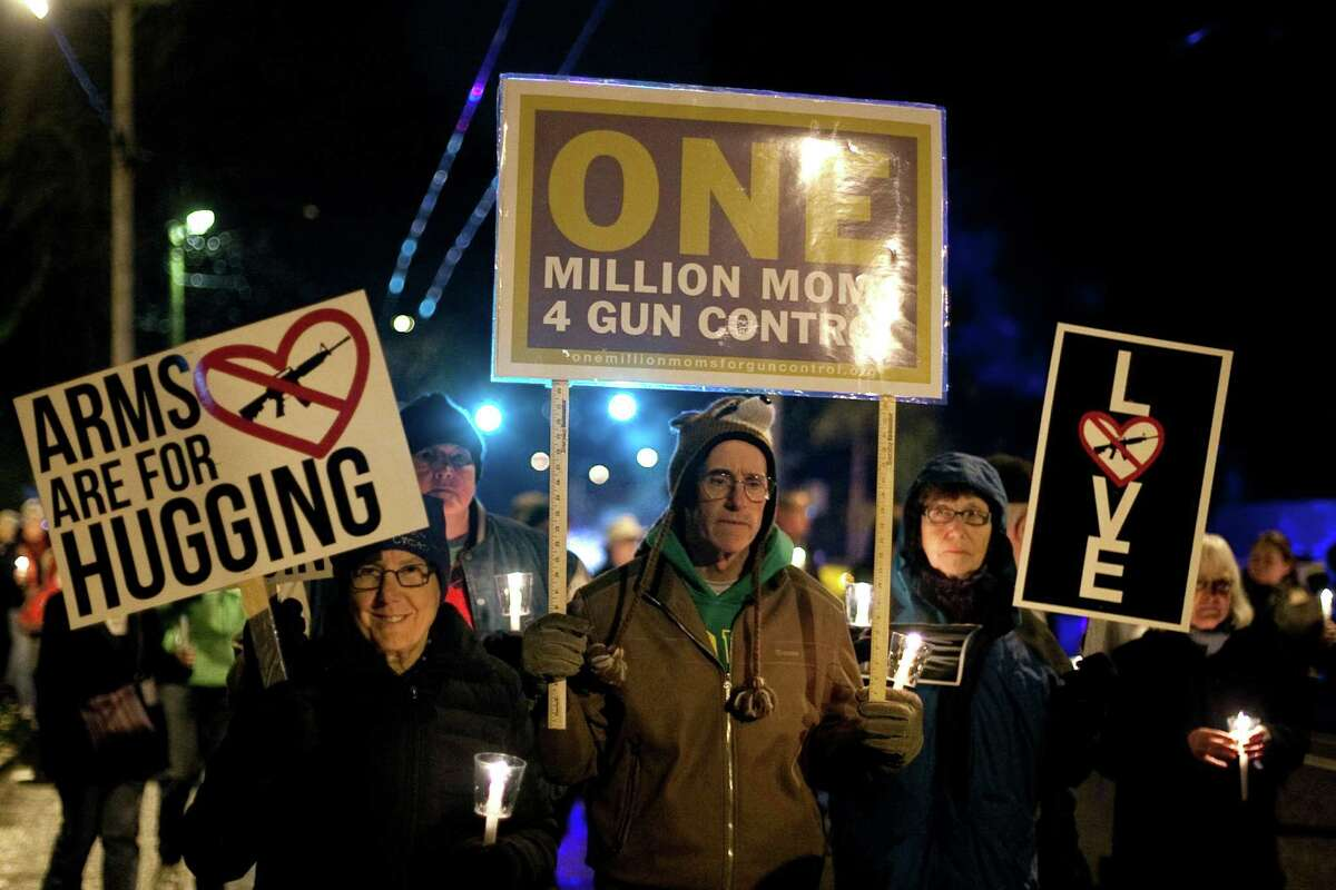 Participants carry signs during an interfaith vigil and march against gun violence in Seattle. Hundreds of people marched with candles from St. Marks Episcopal Cathedral, through Capitol Hill and eventually to St. James Catholic Cathedral.