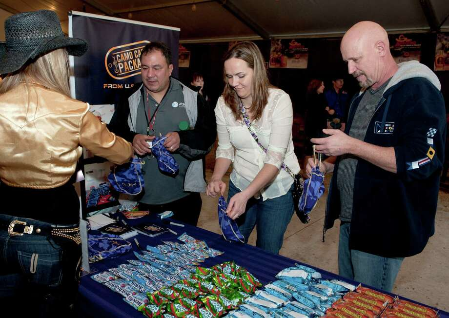 Rodeo fans pack Crown Royal CAMO Care Packages to be sent to active-duty troops overseas, Saturday, Feb. 9, 2013, at the San Antonio Stock Show and Rodeo. Photo: Darren Abate, Associated Press / AP Images