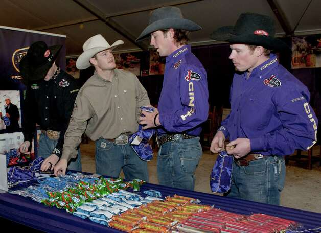 Crown Royal Riders Steve Woolsey (from right), Tilden Hooper, Cody Whitney and Wesley Silcox pack Crown Royal CAMO Care Packages, Saturday, Feb. 9, 2013, at the San Antonio Stock Show and Rodeo. Photo: Darren Abate, Associated Press / AP Images