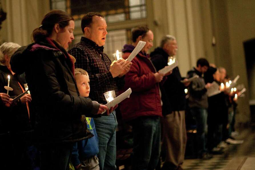 People sing in St. James Cathedral during an interfaith vigil and march against gun violence.