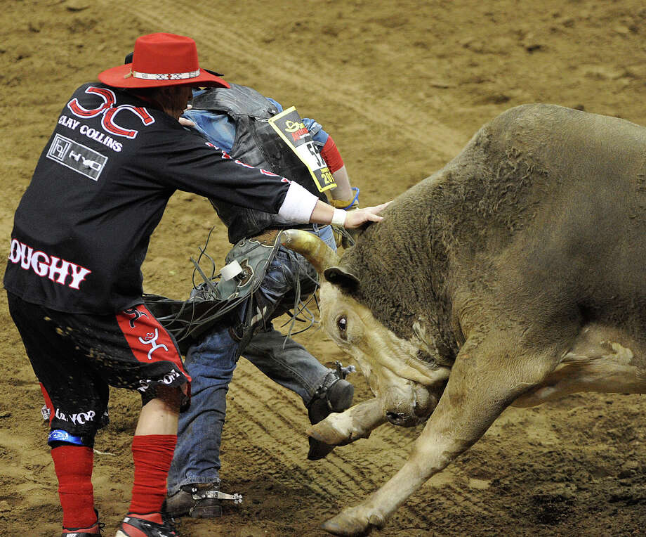 Bullfighter Clay Collins, left, saves bull rider Clay Campbell during the third day of Stock Show & Rodeo on Saturday, Feb. 9, 2013. Photo: Billy Calzada, San Antonio Express-News / San Antonio Express-News