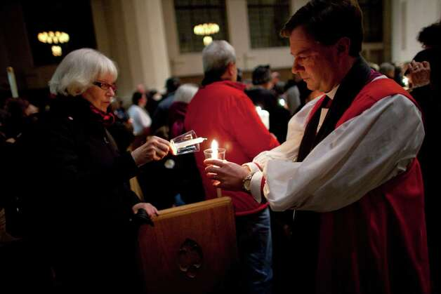 Episcopal Bishop Greg Rickel lights candles before interfaith march against gun violence.  Catholic and Episcopal bishops once made Seattle a national model in ecumenical cooperation.  Now, Catholic Archbishop J. Peter Sartain stands aloof from such witnesses as Saturday's march.. Photo: JOSHUA TRUJILLO, SEATTLEPI.COM / SEATTLEPI.COM