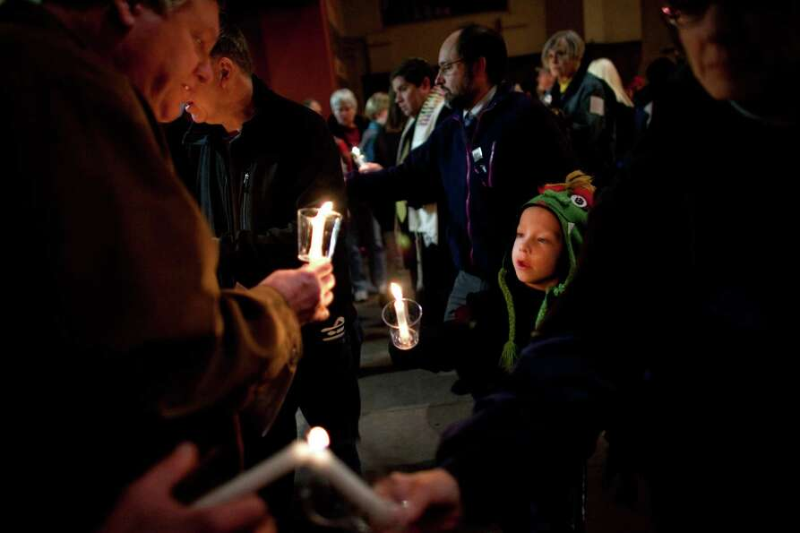Franklin Heymann, 6, lights his candle during an interfaith vigil and march against gun violence at