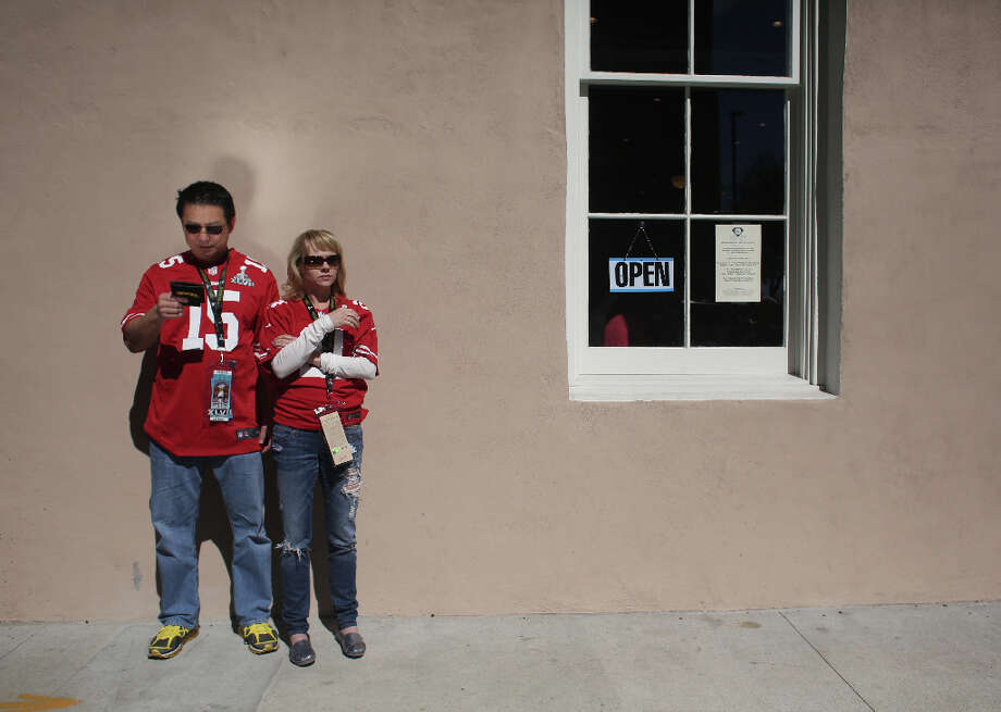 Charles Huang and Paula Kosik, of West Palm Beach Fl., make their way to Super Bowl XLVII between the San Francisco 49ers and the Baltimore Ravens at the Mercedes-Benz Superdome on Sunday February 3, 2013, New Orleans, La. Photo: Mike Kepka, The Chronicle / ONLINE_YES