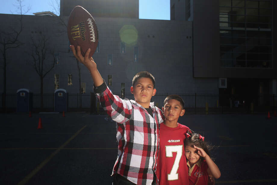 Tailgating outside the Mercedes-Benz Superdome, Randy Cintron, 12, and Tito Ibarra, 9, of Immokalee, Fl., hold a prized football  before Super Bowl XLVII between the San Francisco 49ers and the Baltimore Ravens at the on Sunday February 3, 2013, New Orleans, La. Photo: Mike Kepka, The Chronicle / ONLINE_YES