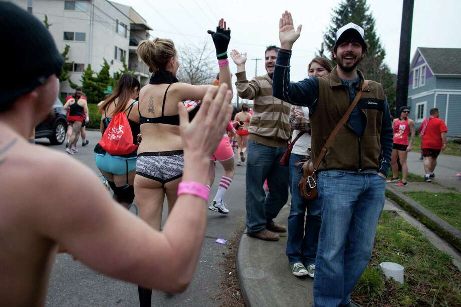 Passersby encourage participants during Cupid's Undie Run in Seattle's Fremont neighborhood. Hundreds of people gathered at the Ballroom and then completed a roughly mile-long run in their skivvies. The event was a fundraiser for The Children's Tumor Foundation. Photo: JOSHUA TRUJILLO, SEATTLEPI.COM / SEATTLEPI.COM