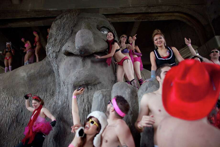Participants gather on the Fremont Troll during Cupid's Undie Run. Dozens of the participants climbed atop the iconic troll under the Aurora Bridge. Photo: JOSHUA TRUJILLO, SEATTLEPI.COM / SEATTLEPI.COM