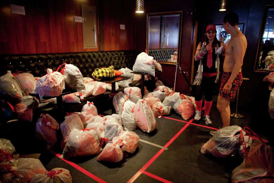 Participants check in their clothes during Cupid's Undie Run at the Ballroom in Seattle's Fremont neighborhood. Hundreds of people gathered at the Ballroom and then completed a roughly mile-long run in their skivvies. The event was a fundraiser for The Children's Tumor Foundation. Photo: JOSHUA TRUJILLO, SEATTLEPI.COM / SEATTLEPI.COM