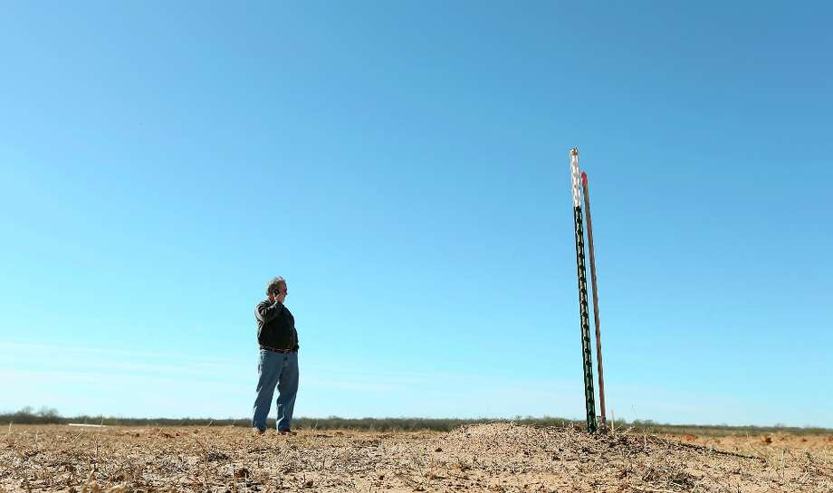 Harvey Howell, president of H.H. Howell, Inc., an oil and gas exploration company in San Antonio, calls to check the status of the arrival of a drilling rig at a site in Frio County, Thursday, Jan. 17, 2013. The third generation wildcatter was investing $1.3 million in the drilling operation, marked by the stake in the foreground. He calculated his odds at finding oil at 10-1 against. Photo: Jerry Lara, San Antonio Express-News / © 2013 San Antonio Express-News