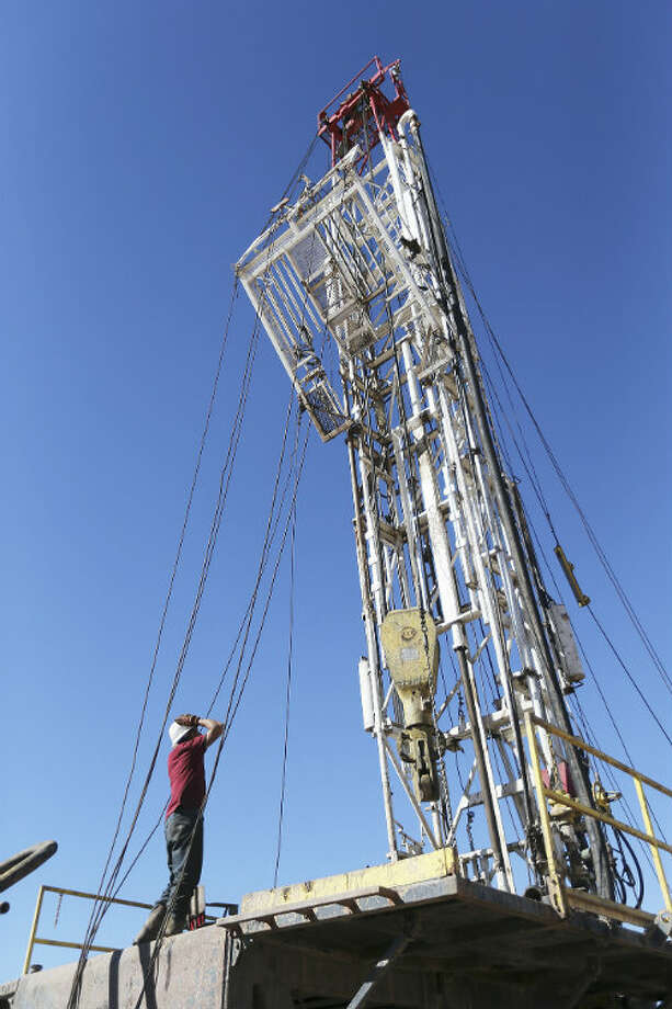 Anatolio Salinas watches the rigging as the monkey board is set in place on a rig at the drilling site in Frio County near Moore, Texas. The monkey board is used by the derrickman while moving pipe in or out of the hole.