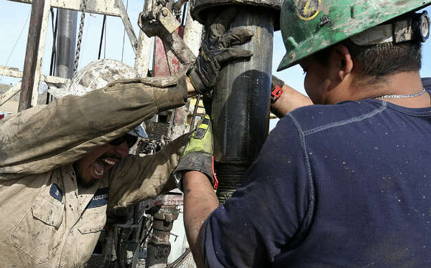Floorhands J.B. Espinoza, left, and Miguel Ortiz, move pipe out of the hole. Espinoza was on his first week on the rig.