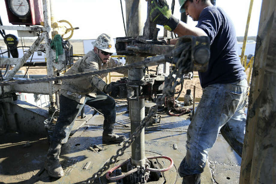 Floorhands J.B. Espinoza, left, and Miguel Ortiz remove pipe at the drilling site.