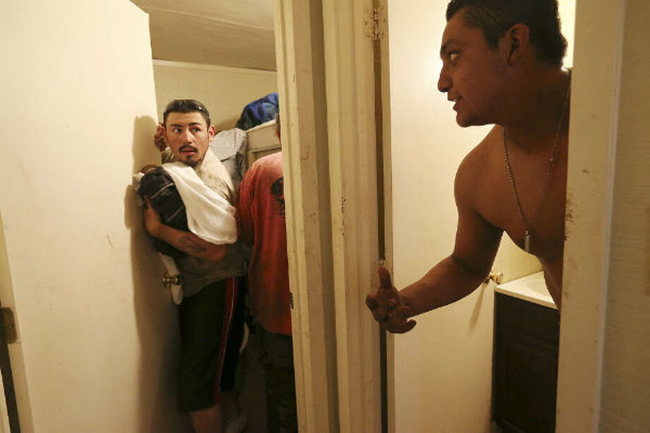 At the end of the 12-hour shift, Miguel Ortiz, 21, right, of Alamo, Texas asks for his towel, as he and fellow floorhand, J.B. Espinoza, 21, of Freer, rush to get to a grocery story 20 miles away. The crew was staying in company-provided housing at the drilling site in Frio County. Midway through their week, they were running out of food and money. They were in rush to reach a Western Union before closing in order to receive money wired to them by their families.