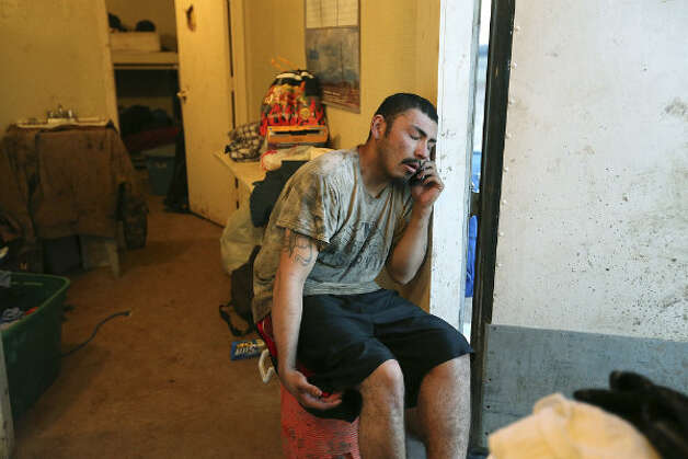 After his shift, floorhand J.B. Espinoza, 21, calls his girlfriend while waiting for his turn to shower inside the company-provided housing at a drilling site in Frio County, Sunday, Jan. 20, 2013. It was Espinoza's first week on the rig.