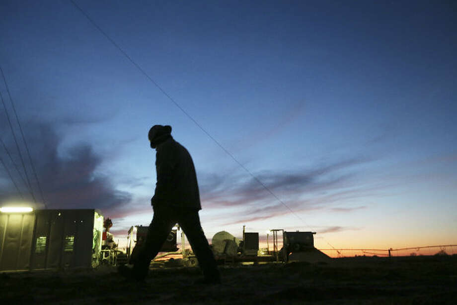 Floorhand Juan Mata, 32, of Alice, Texas walks back to the rig after talking with the toolpusher at the start of the overnight shift at a drilling site in Frio County.