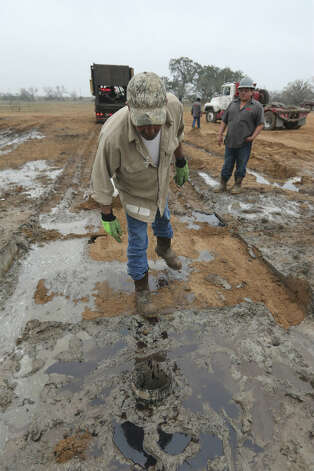 Tool pusher Luis Garcia, 50, of Benavides, Texas, looks at the wellhead, all that remains after Arrow Drilling crews leave a drilling site in Frio County, Saturday, Jan. 26, 2013. The hole was a venture by third-generation wildcatter Harvey Howell, of San Antonio. After a week of drilling for oil, the hole came up dry.