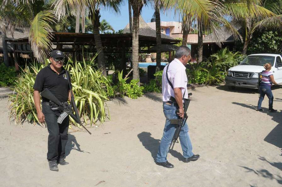 Police patrol on the beach outside a home after masked armed men broke into the home in Acapulco, Me