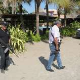 Police patrol on the beach outside a home after masked armed men broke into the home in Acapulco, Mexico, Tuesday. According to the mayor of Acapulco, five masked men burst into the house that Spanish tourists had rented on the outskirts of Acapulco, in a low-key area near the beach, and held a group of six Spanish men and one Mexican woman at gunpoint, while they raped the six Spanish women before dawn on Monday.