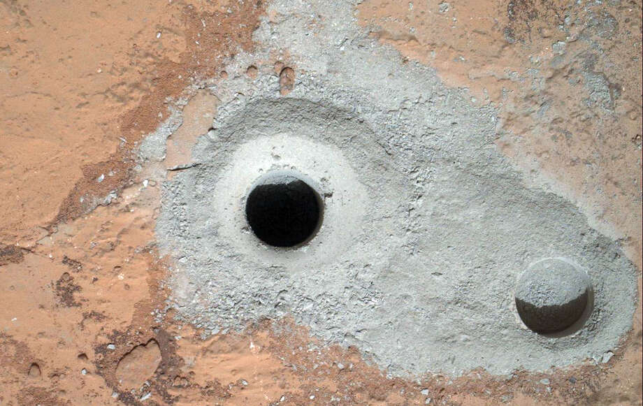 """""""Drill Baby Drill"""" - This image released by NASA on Saturday Feb. 9, 2013 shows a fresh drill hole, center, made by the Curiosity rover on Friday, Feb. 8, 2013 next to an earlier test hole. Curiosity has completed its first drill into a Martian rock, a huge milestone since landing in an ancient crater in August 2012. Photo: AP"""