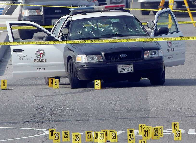 A bullet-damaged Los Angeles Police vehicle is taped off by police on Thursday in Corona, Calif.  Ch