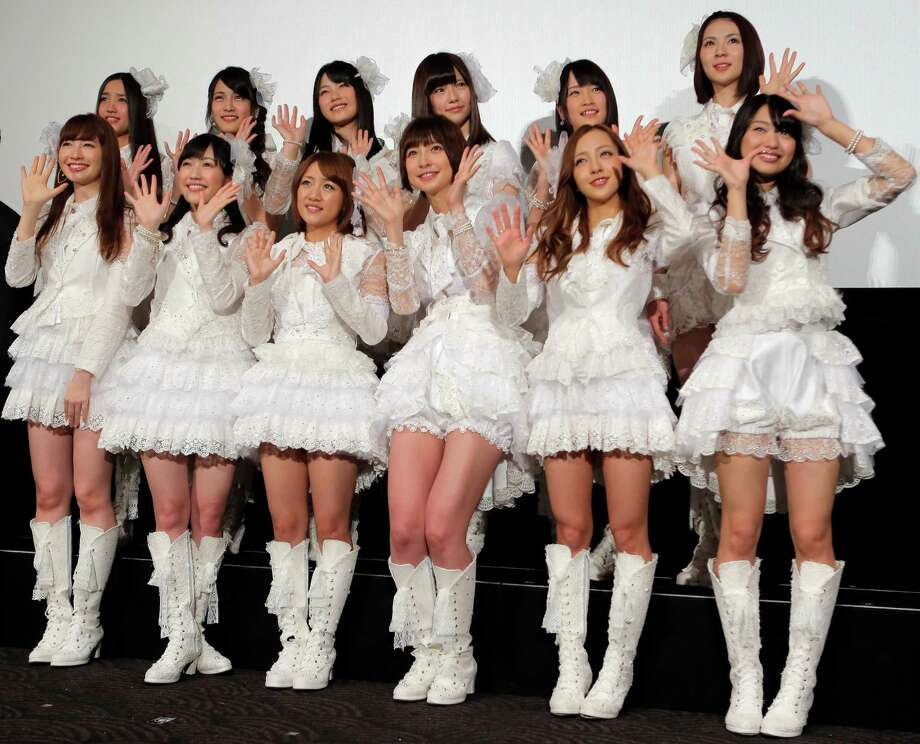 "The hugely popular Japanese girl band AKB48 members, from left in first row pose for photographers at the opening premiere of their new film ""Documentary of AKB48 No Flower Without Rain"" in Tokyo on Feb.1 one day after a group member shaved her head and issued a tearful videotaped apology for violating the megagroup's no-dating rule. The spectacle has sparked debate in Japan over whether the band AKB48 exerts too much control over its performers. Minami Minegishi made the video, posted on AKB48's website, after the 20-year-old was caught by a gossip magazine coming out of her boyfriend's apartment. AKB48 says it forbids its members from dating to project a clean image and signal their devotion to the group and their mostly male fans. Photo: AP"