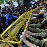 Indian police reinforce their barricades during a protest by left leaning student organizations against Gujarat chief minister Narendra Modi outside the Shri Ram College of Commerce in New Delhi, India, Wednesday. Modi was at the college to address students.