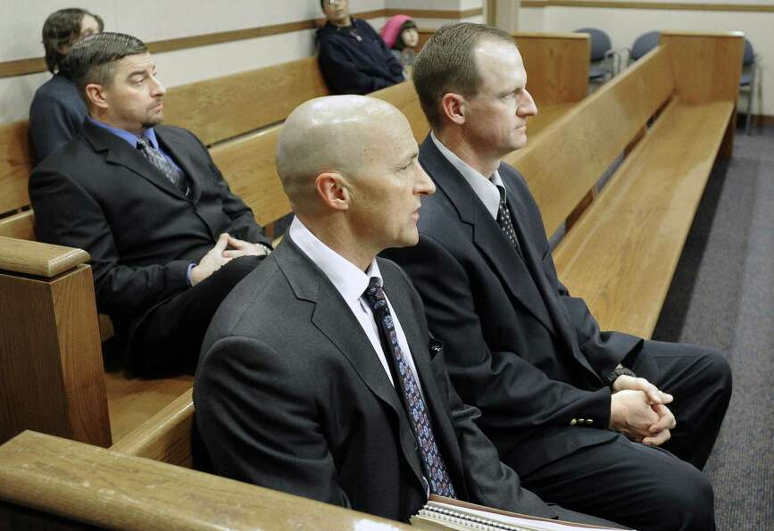 Attorney Patrick Mulligan, front, sits with former Boulder Police officers Samuel Carter, left, and