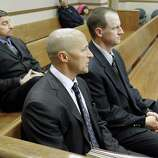 Attorney Patrick Mulligan, front, sits with former Boulder Police officers Samuel Carter, left, and Brent Curnow, right, during the filing of charges on Thursday at the Boulder County Jail in Boulder, Colo. Carter and Curnow are being charged for the killing of a bull elk on Mapelton Avenue in Boulder on Jan. 1. (AP Photo/The Daily Camera, Jeremy Papasso)