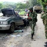 A soldier takes a photograph of a vehicle that exploded in El Palo, southern Colombia, Tuesday.  Gen. Humberto Jerez, the local military commander, said that two car bombs were set off by rebels of the Revolutionary Armed Forces of Colombia, FARC, killing one man.