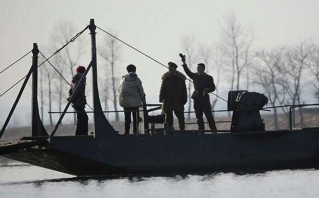A North Korean soldier, right, stands with others on the barge on the river bank of the North Korean town of Sinuiju, opposite side of Dandong, China on Wednesday. North Korea vowed last month to carry out its third nuclear test but has said nothing about timing. As a result, the building suspense in Seoul has prompted many to look at the dates Pyongyang has chosen for past atomic tests, as well as rocket and missile launches. Photo: AP