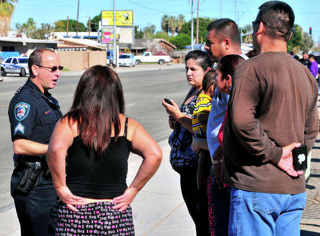 Yuma Police Sgt. Clint Norad talks with a group of concerned parents across the street from Salida Del Sol Elementary School, Tuesday in Yuma, Ariz. Salida Del Sol and Rancho Viejo Elementary were on lockdown after Yuma police responded to an unconfirmed report of a student possibly armed with a gun at Rancho Viejo. Photo: AP