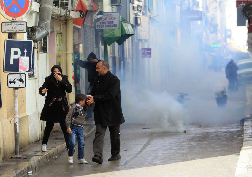 A family flees tear gas during a demonstration in Tunis, Thursday. The Islamist party dominating Tun