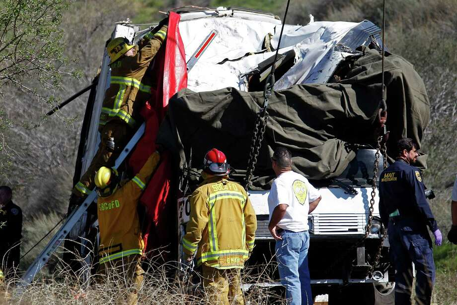 A firefighter adjusts a tarp to cover a victim inside after a tow truck lifted a tour bus back onto the road Monday. The bus collided with two other vehicles and crashed Sunday, killing at least eight people and injuring 38, on Highway 38 just north of Yucaipa, Calif.  The bus was carrying a tour group from Tijuana, Mexico. Photo: AP