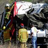 A firefighter adjusts a tarp to cover a victim inside after a tow truck lifted a tour bus back onto the road Monday. The bus collided with two other vehicles and crashed Sunday, killing at least eight people and injuring 38, on Highway 38 just north of Yucaipa, Calif.  The bus was carrying a tour group from Tijuana, Mexico.